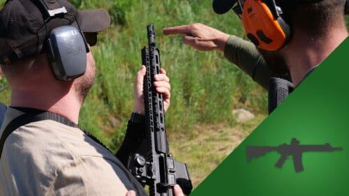 Szkolenie strzeleckie karabin podstawowy CMMS. Instruktor pokazuje kursantowi podstawową postawę strzelecką high ready.